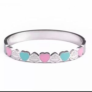Silver bracelet with blue and pink hearts